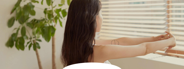 올리브색 레깅스와 하얀 민소매 운동복을 입은 긴머리의 여성이 양팔을 깍지끼고 창문을 향해서 스트레칭하고 있는 뒷모습의 사진