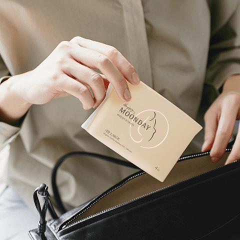검정 가방에서 생리대를 꺼내는 여성의 손이 확대된 사진