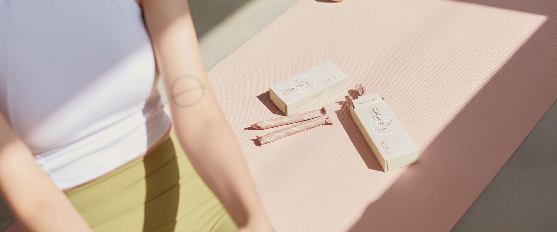 분홍 요가매트에 앉아있는 여성 뒤로 탐폰패키지 2개가 놓여있는 사진. 햇볕이 창문으로 들어옴.