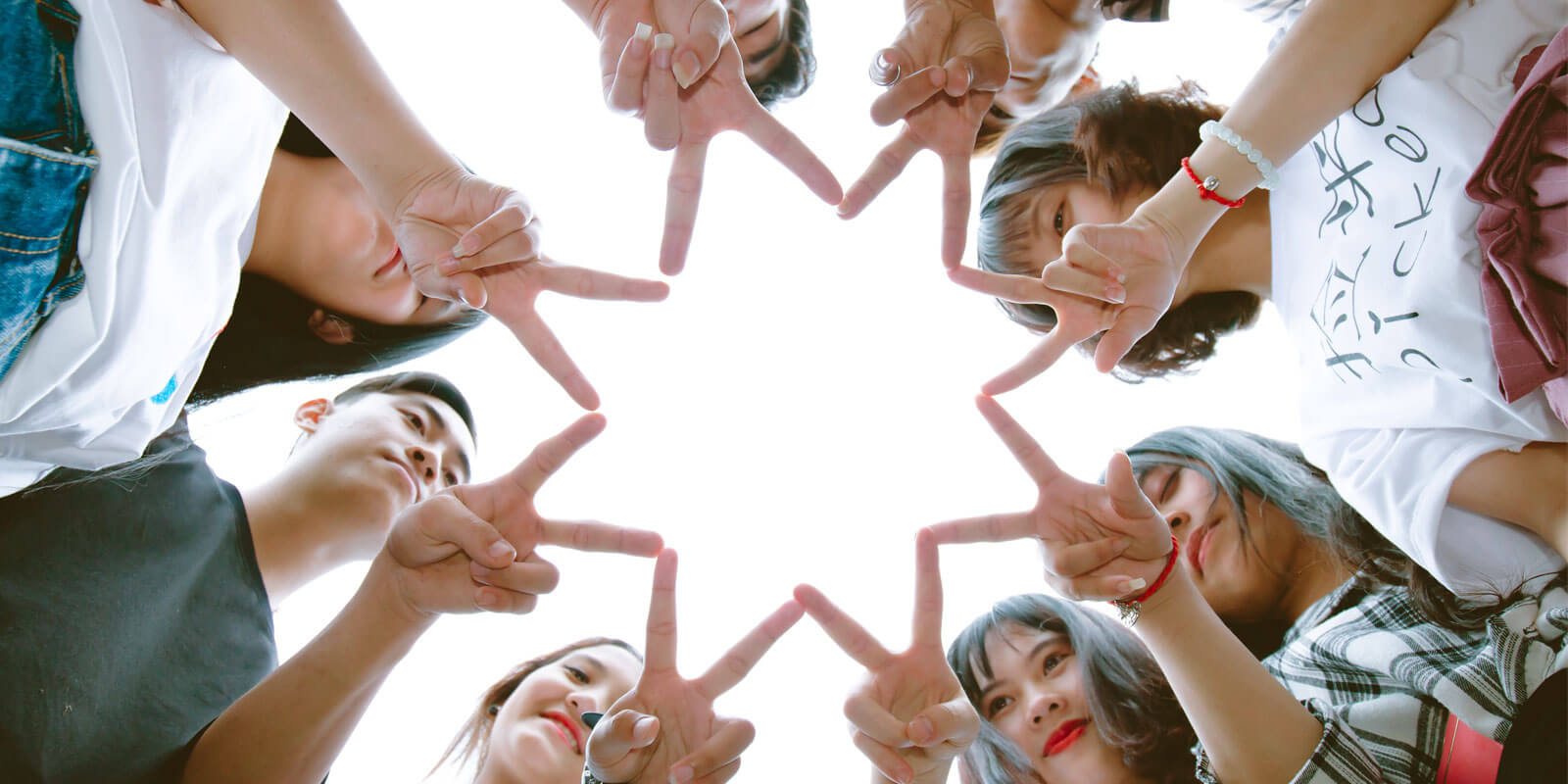 8명의 아이들이 손가락을 모아 별모양을 만든 모습을 아래에서 위로 찍은 사진